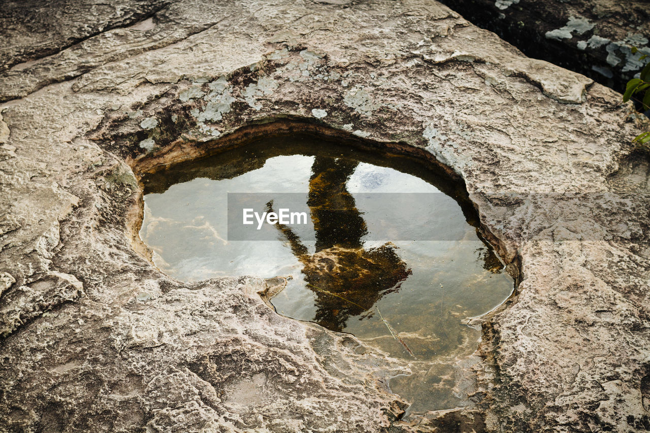 Reflection Of Man In Water On Rock Formation