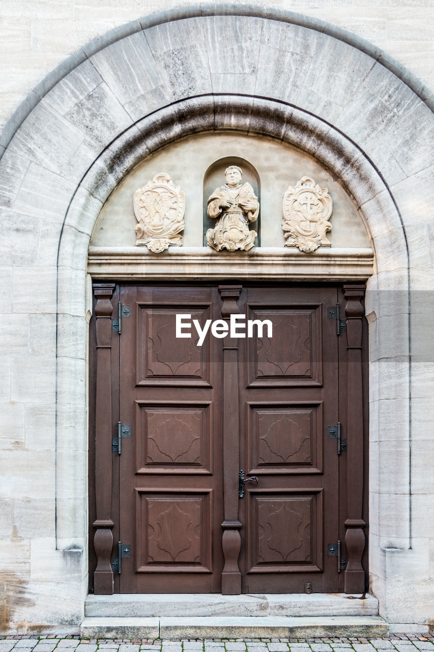 entrance, door, architecture, closed, built structure, building exterior, no people, representation, protection, art and craft, safety, day, security, human representation, arch, building, creativity, wood - material, craft, male likeness, outdoors, wood, bas relief