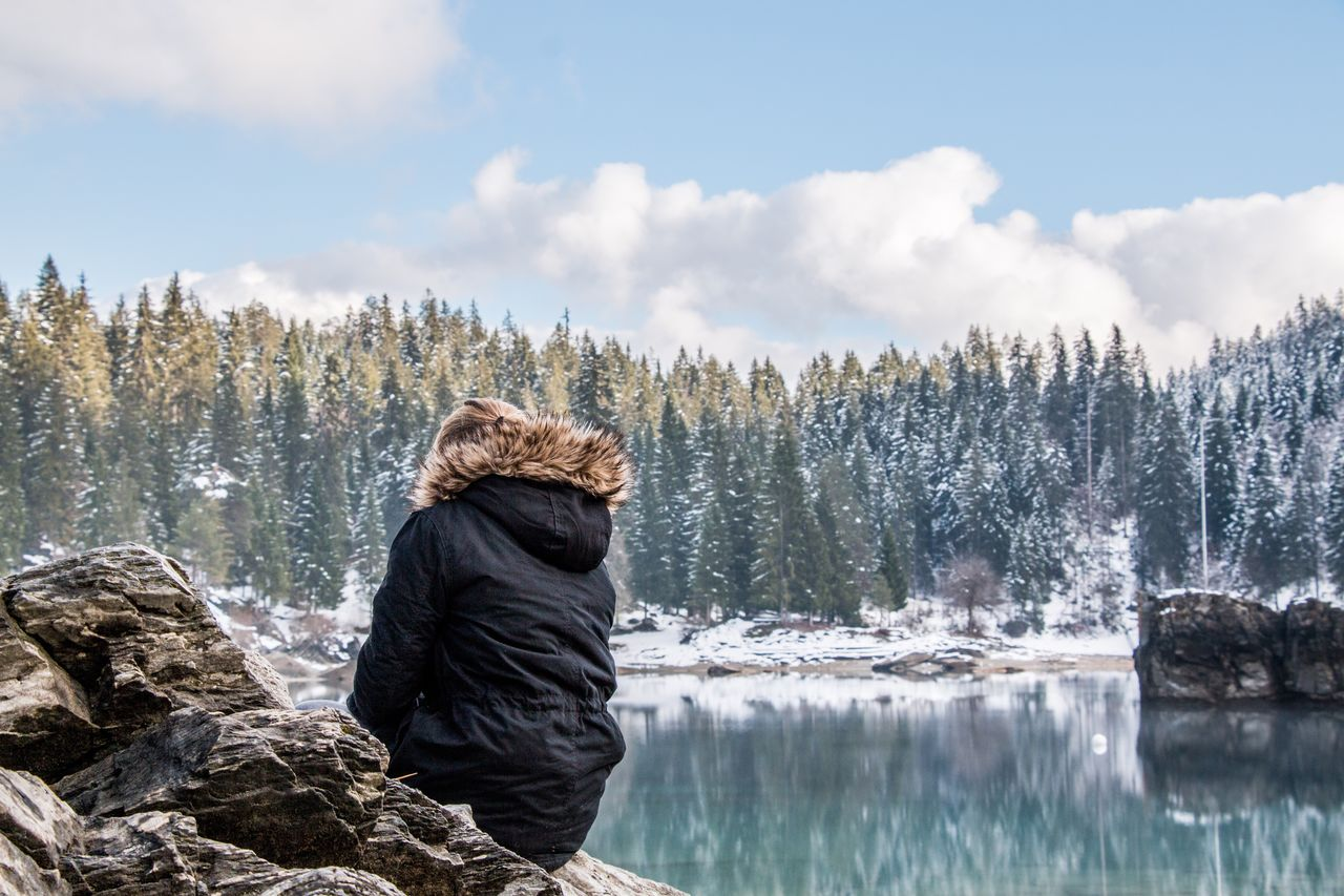 Rear View Of Woman Sitting On Forest Lake In Winter