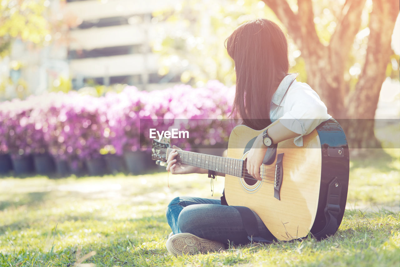 MIDSECTION OF WOMAN SITTING ON FIELD WITH GUITAR