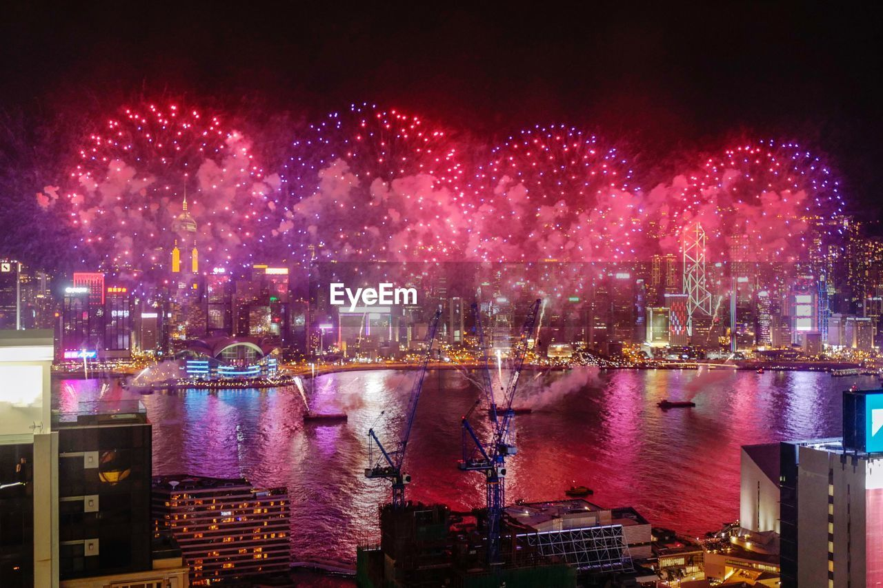 night, water, illuminated, building exterior, architecture, built structure, city, river, no people, nature, reflection, motion, pink color, sky, multi colored, firework display, firework, outdoors, celebration, cityscape, office building exterior, light, skyscraper, firework - man made object, purple