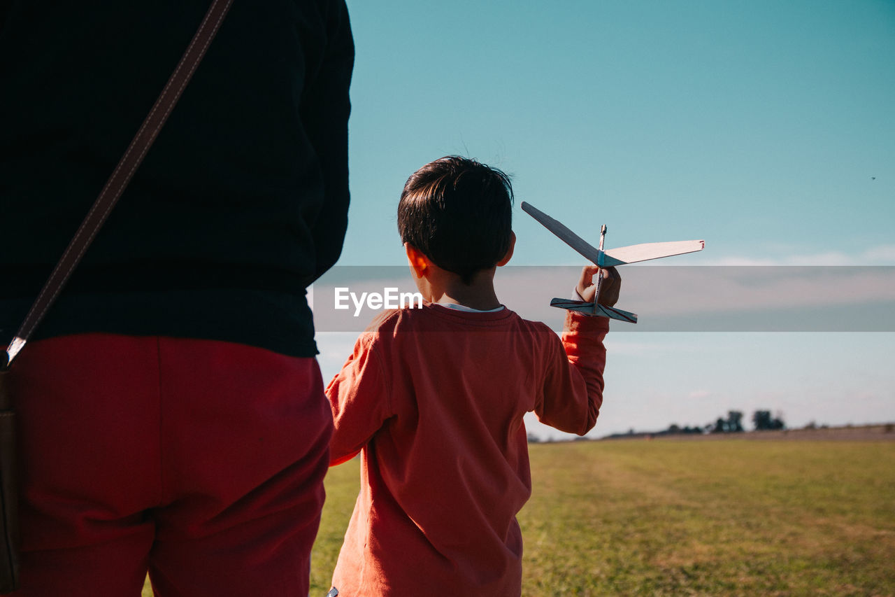 Rear view of mother and son on land against sky