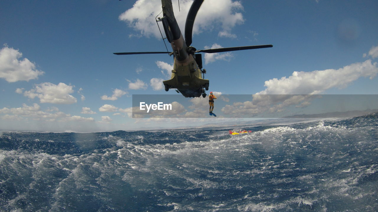 Person Jumping In Sea From Helicopter Against Sky