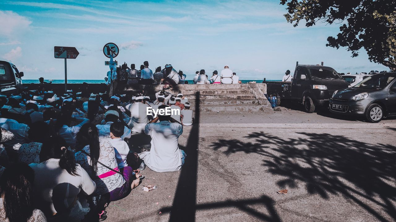 group of people, real people, large group of people, crowd, men, nature, land vehicle, transportation, day, sky, lifestyles, sunlight, mode of transportation, shadow, women, leisure activity, land, motor vehicle, cloud - sky, outdoors