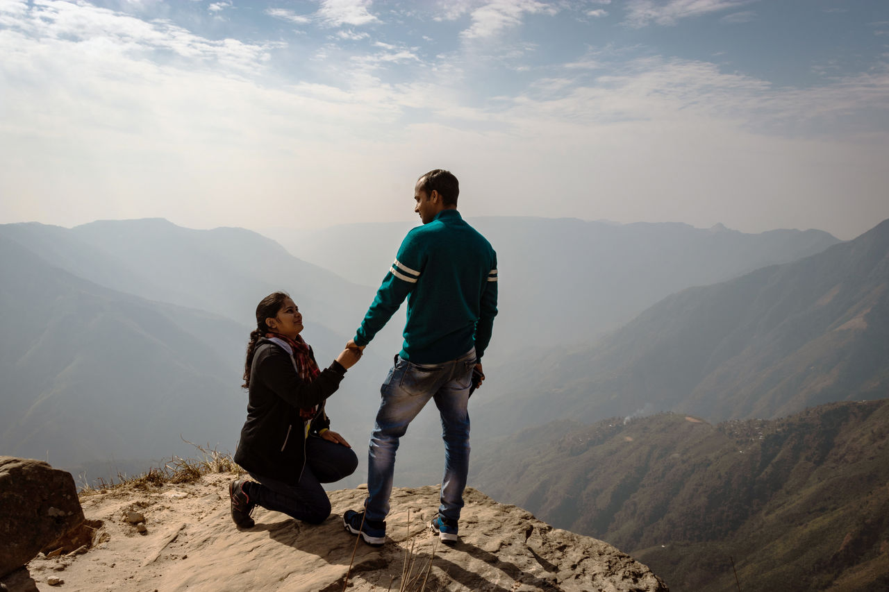 Woman proposing man on cliff against sky