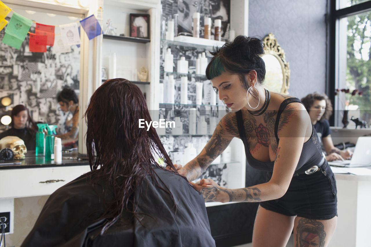 A hairdresser styling a customer's hair.