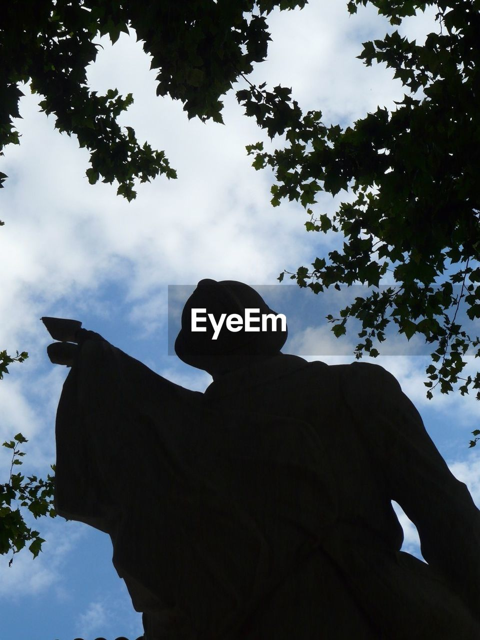 low angle view, silhouette, sky, statue, human representation, tree, sculpture, cloud - sky, outdoors, day, no people, nature