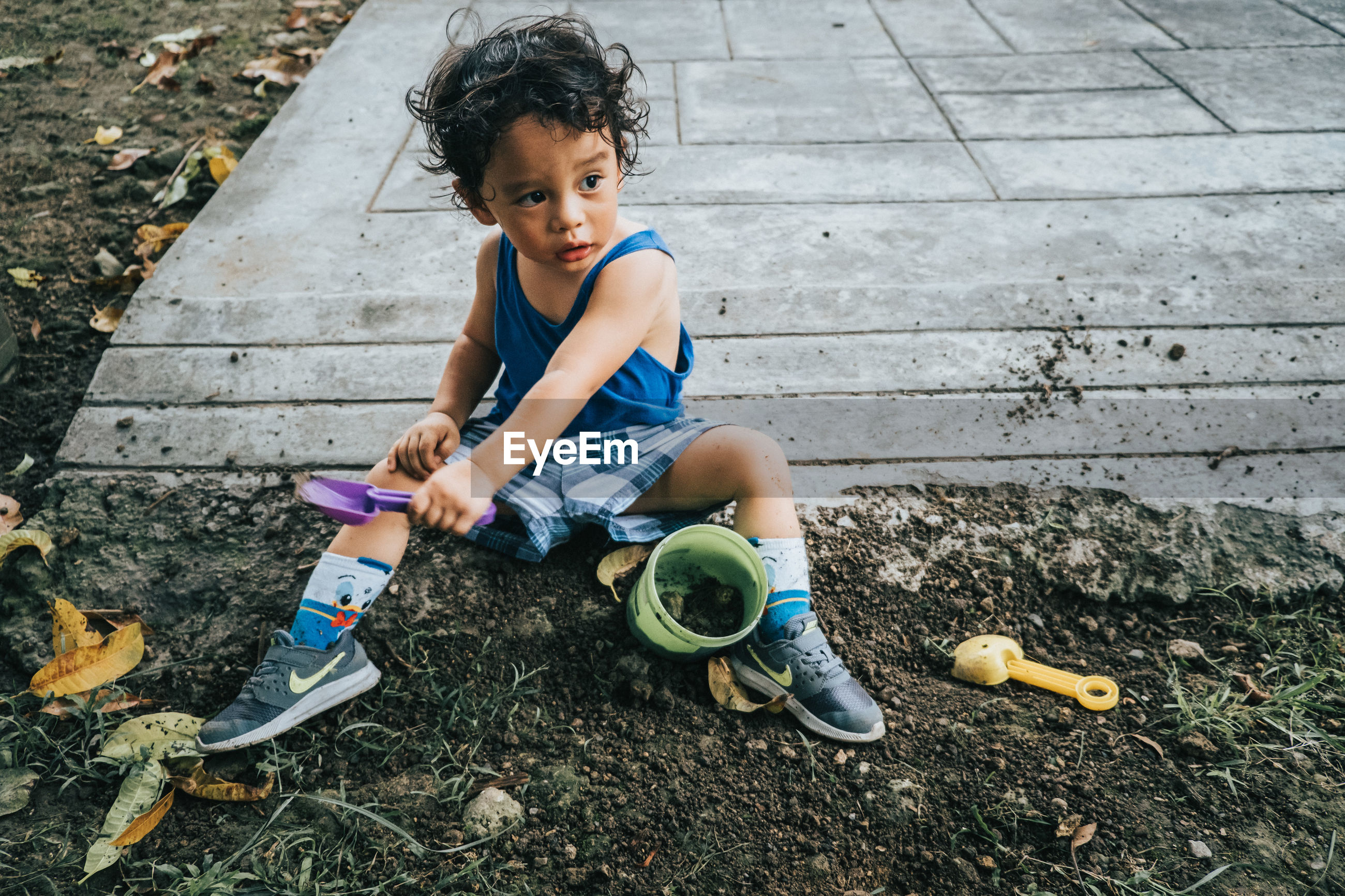 HIGH ANGLE VIEW OF CUTE BOY PLAYING WITH TOY SITTING