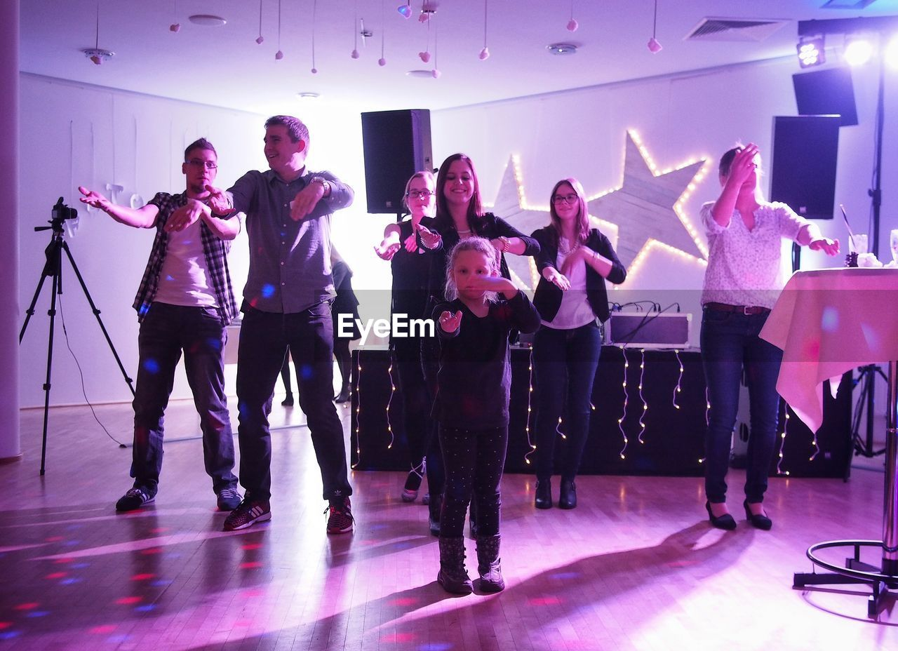 indoors, full length, medium group of people, men, dancing, arts culture and entertainment, fun, women, nightclub, togetherness, performance, cheerful, nightlife, standing, glamour, occupation, real people, illuminated, party - social event, young adult, young women, adult, day, adults only, people