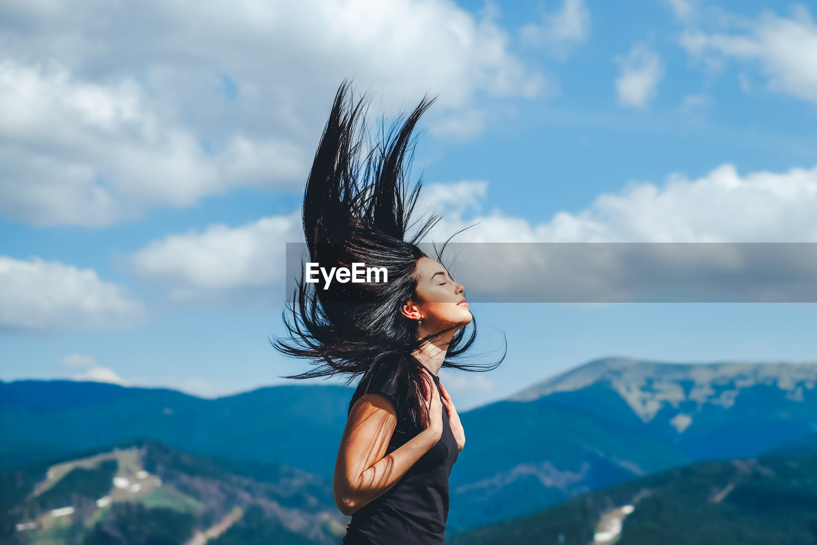 Side view of mid adult woman with eyes closed standing on mountain against cloudy sky