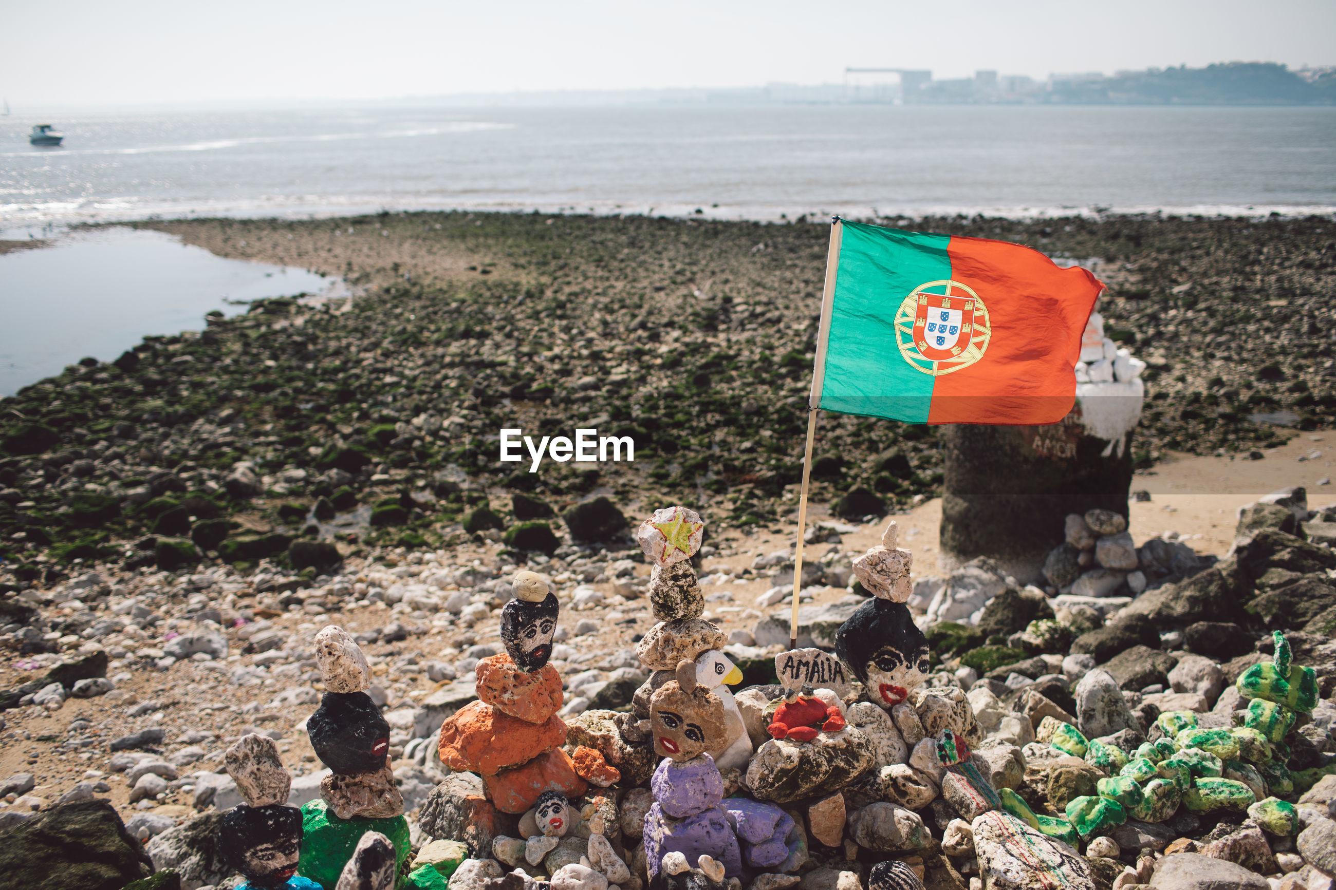 Flag waving on rocks at beach
