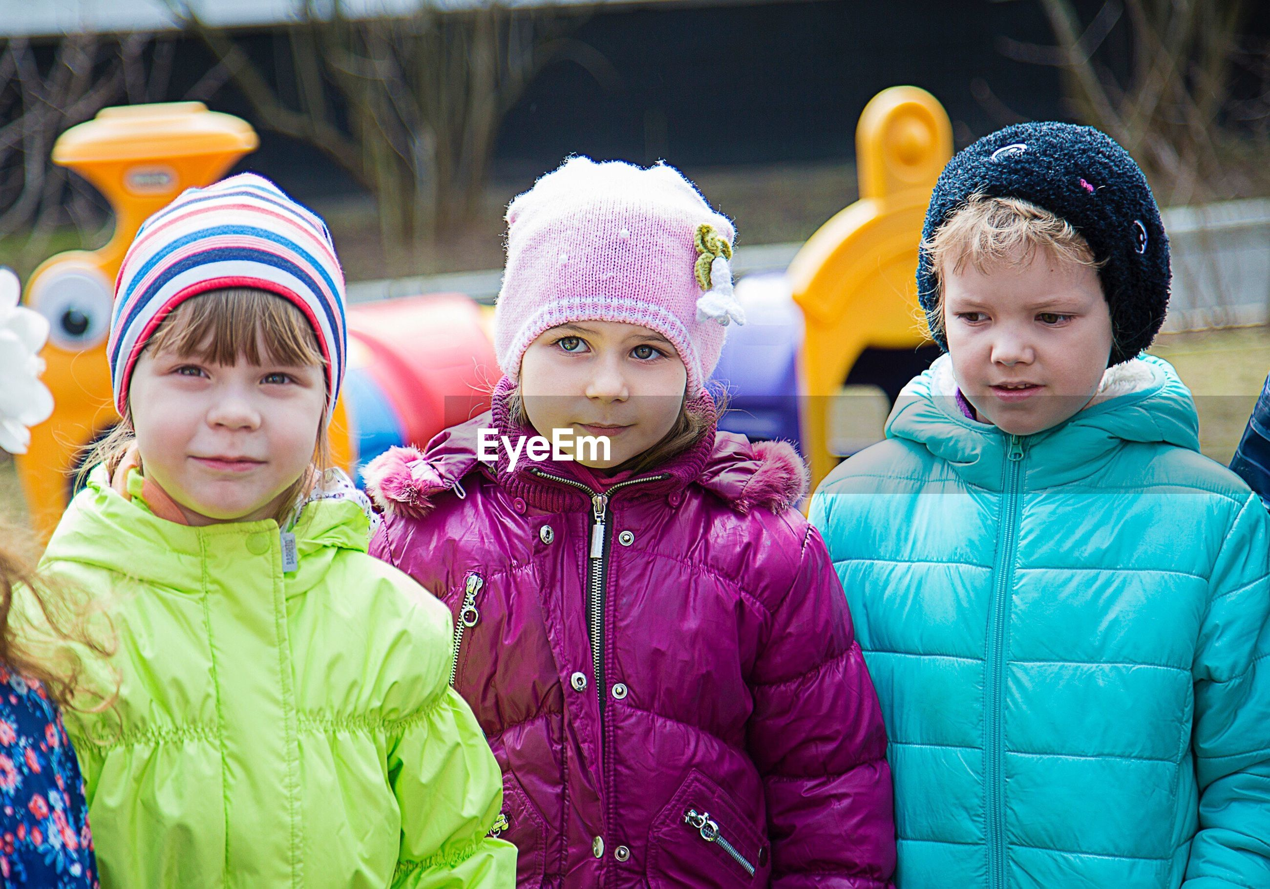 elementary age, childhood, girls, front view, leisure activity, smiling, lifestyles, togetherness, innocence, sibling, mask - disguise, fun, multi colored, focus on foreground, colorful