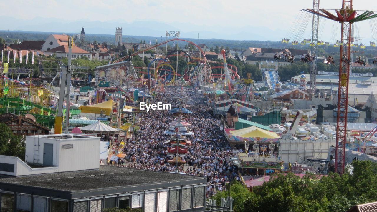 Crowd At Amusement Park Against Sky
