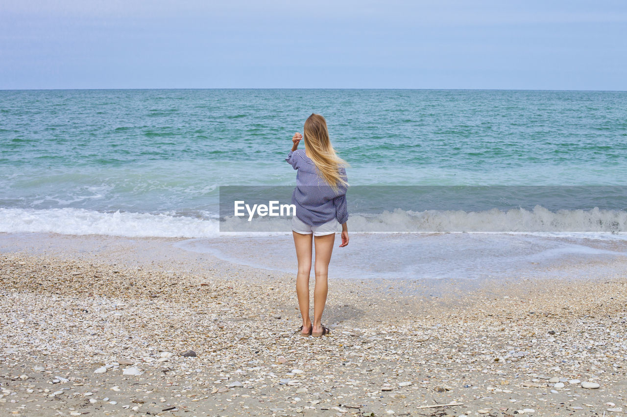 sea, beach, land, water, horizon over water, horizon, one person, beauty in nature, scenics - nature, sky, leisure activity, lifestyles, rear view, standing, real people, full length, tranquil scene, women, tranquility, hair, outdoors, hairstyle
