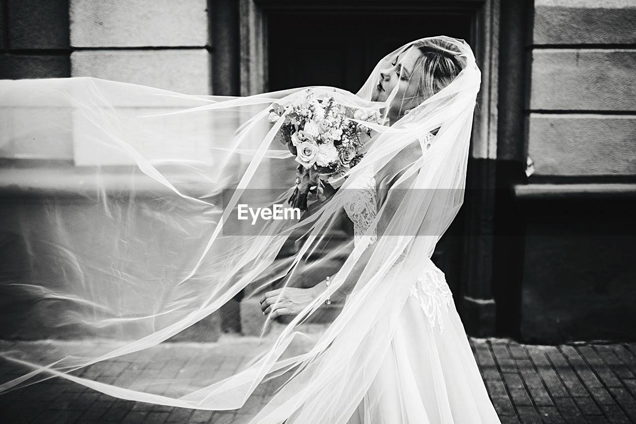 Side View Of Bride Standing In Wedding Dress On Footpath
