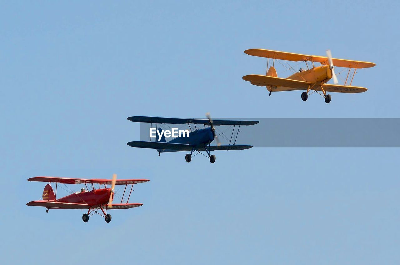 Three Biplanes Flying In Sky