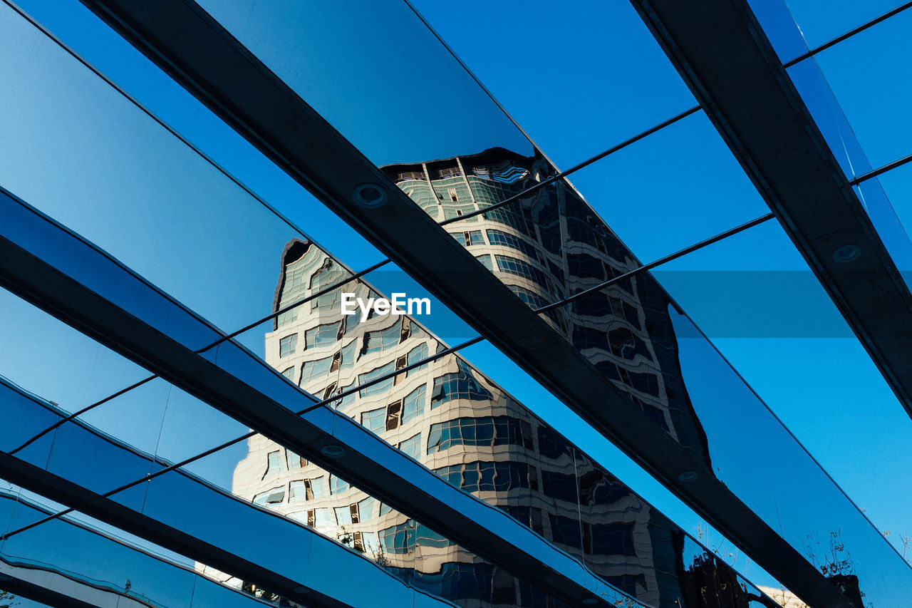 low angle view, architecture, built structure, blue, connection, day, building exterior, modern, bridge - man made structure, city, no people, outdoors, clear sky, skyscraper, sky