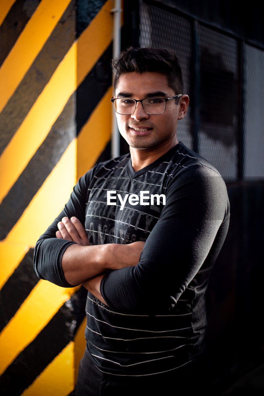 looking at camera, one person, portrait, casual clothing, standing, young adult, young men, front view, real people, glasses, indoors, men, arms crossed, lifestyles, waist up, black color, confidence, striped