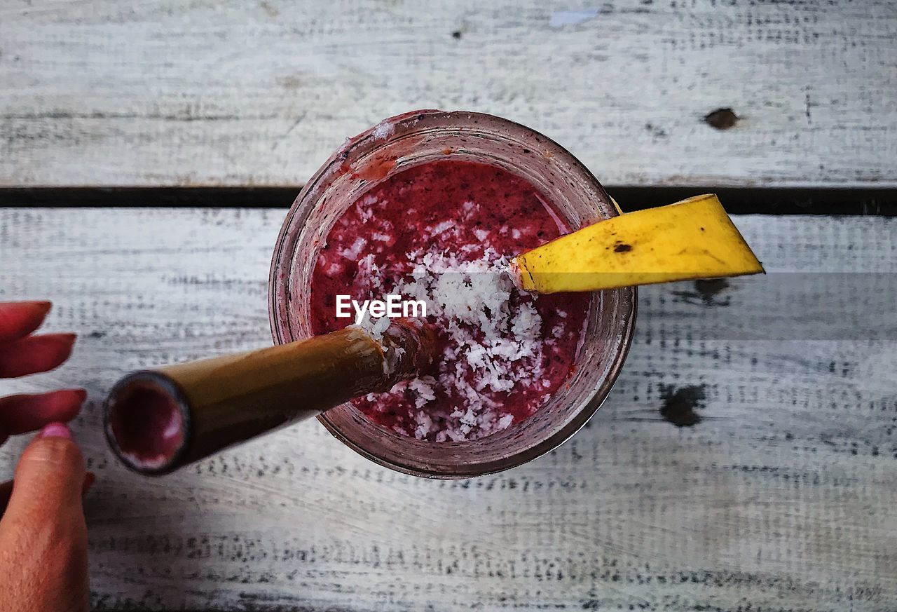 food and drink, human hand, healthy eating, food, hand, human body part, one person, freshness, indoors, wellbeing, kitchen utensil, wood - material, fruit, high angle view, spoon, eating utensil, close-up, holding, smoothie, household equipment, finger, glass, mash - food state