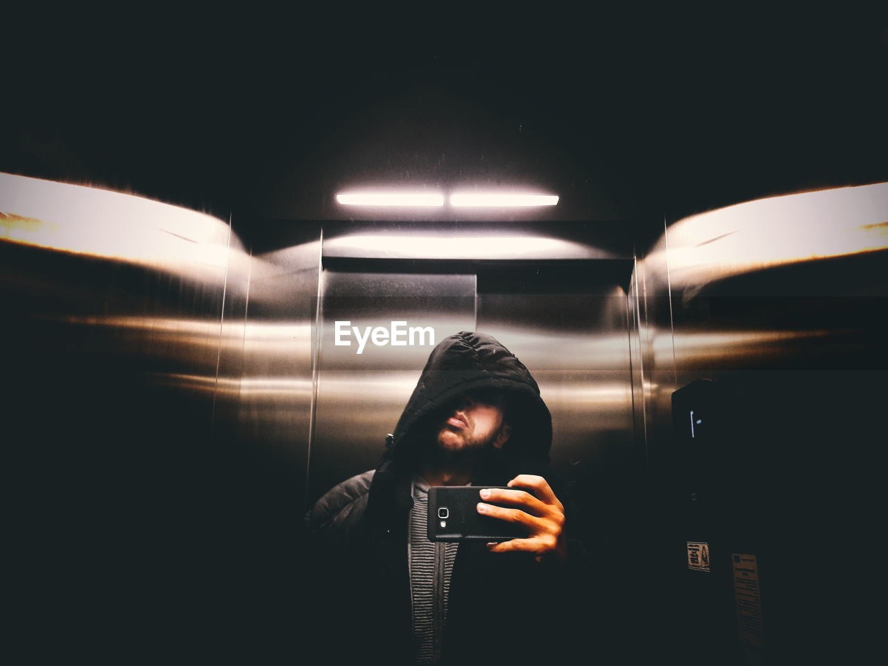 Young Man Taking Selfie With Smart Phone While Standing In Elevator