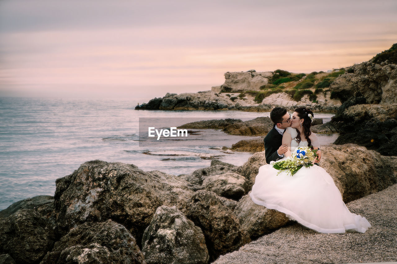 Wedding Couple Kissing While Sitting At Rocky Beach