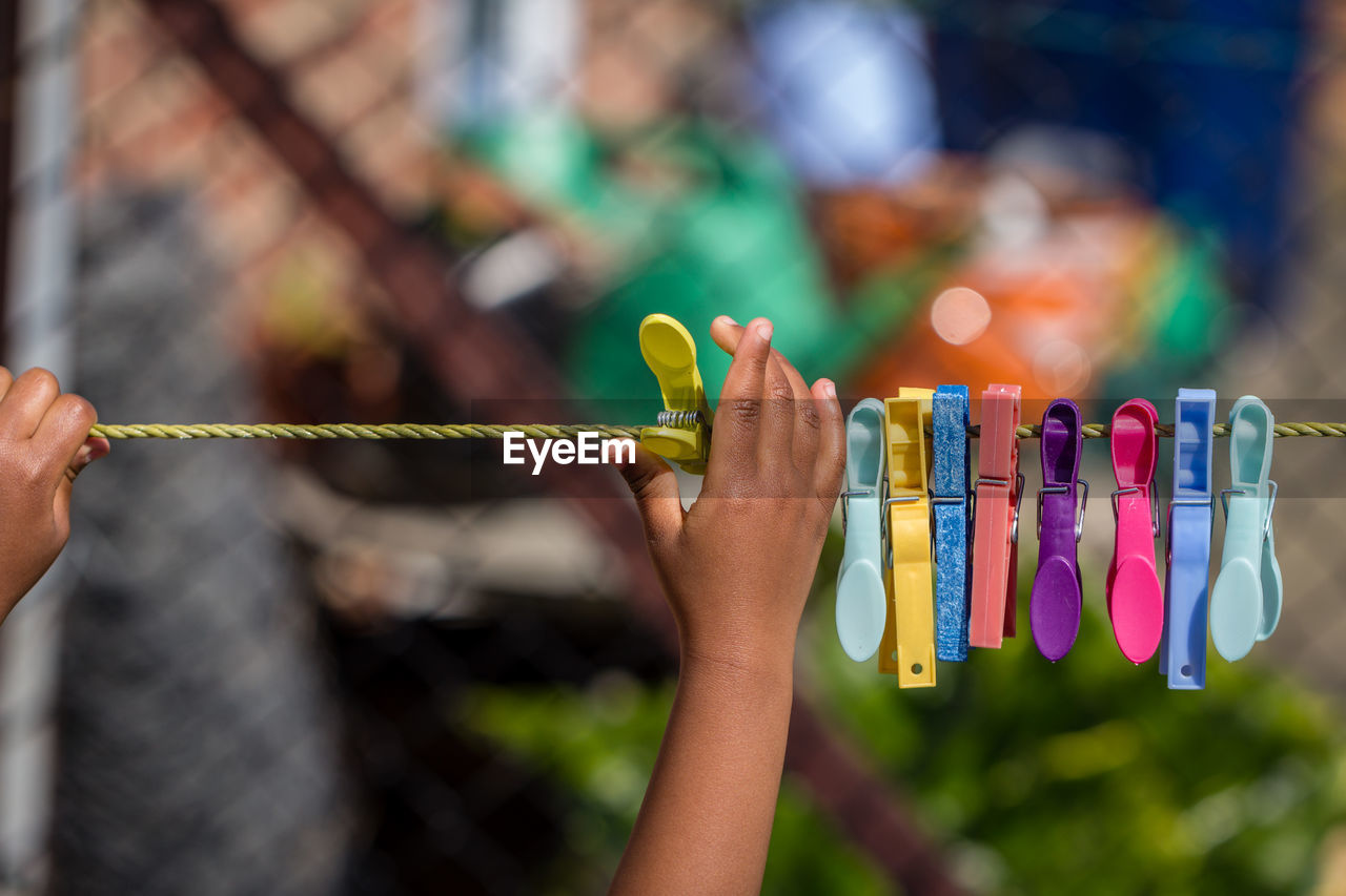 Close-Up Of Hand Touching Clothespins Hanging On Clothesline