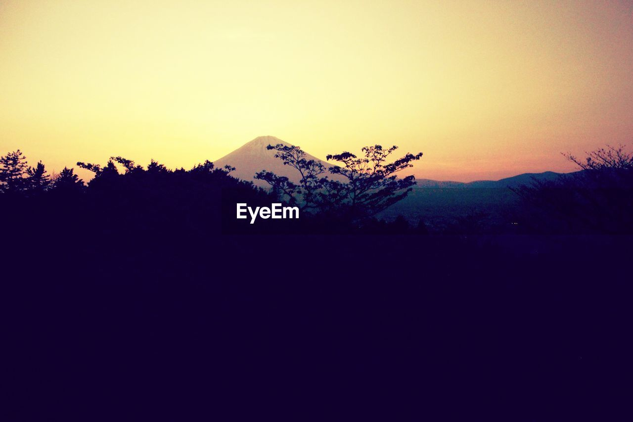 sky, sunset, tranquil scene, mountain, scenics - nature, tranquility, copy space, beauty in nature, landscape, silhouette, nature, environment, tree, non-urban scene, no people, clear sky, mountain range, orange color, plant, idyllic, outdoors, mountain peak