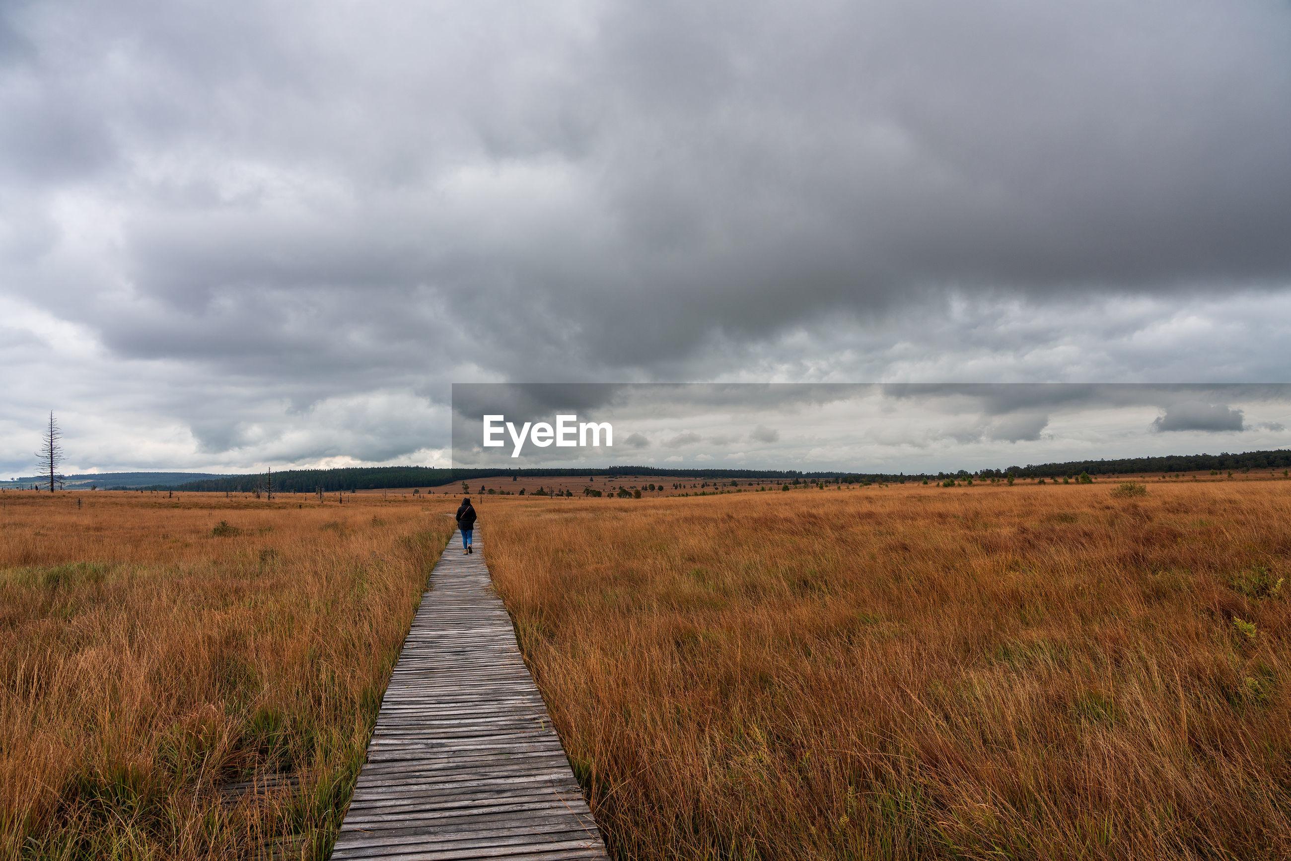Rear view of woman walking on boardwalk along grassy land against cloudy sky