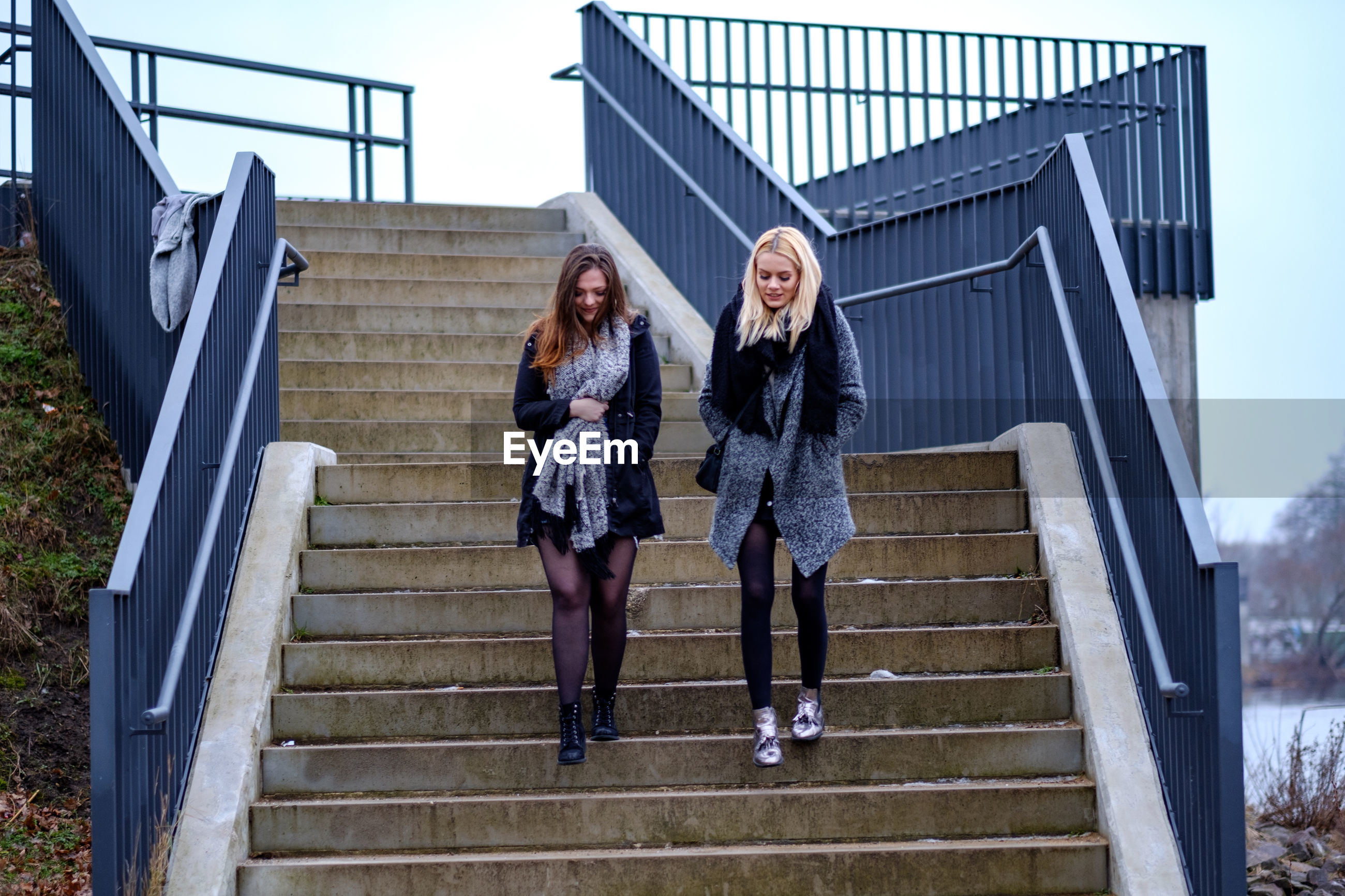 Young women walking on staircase against sky