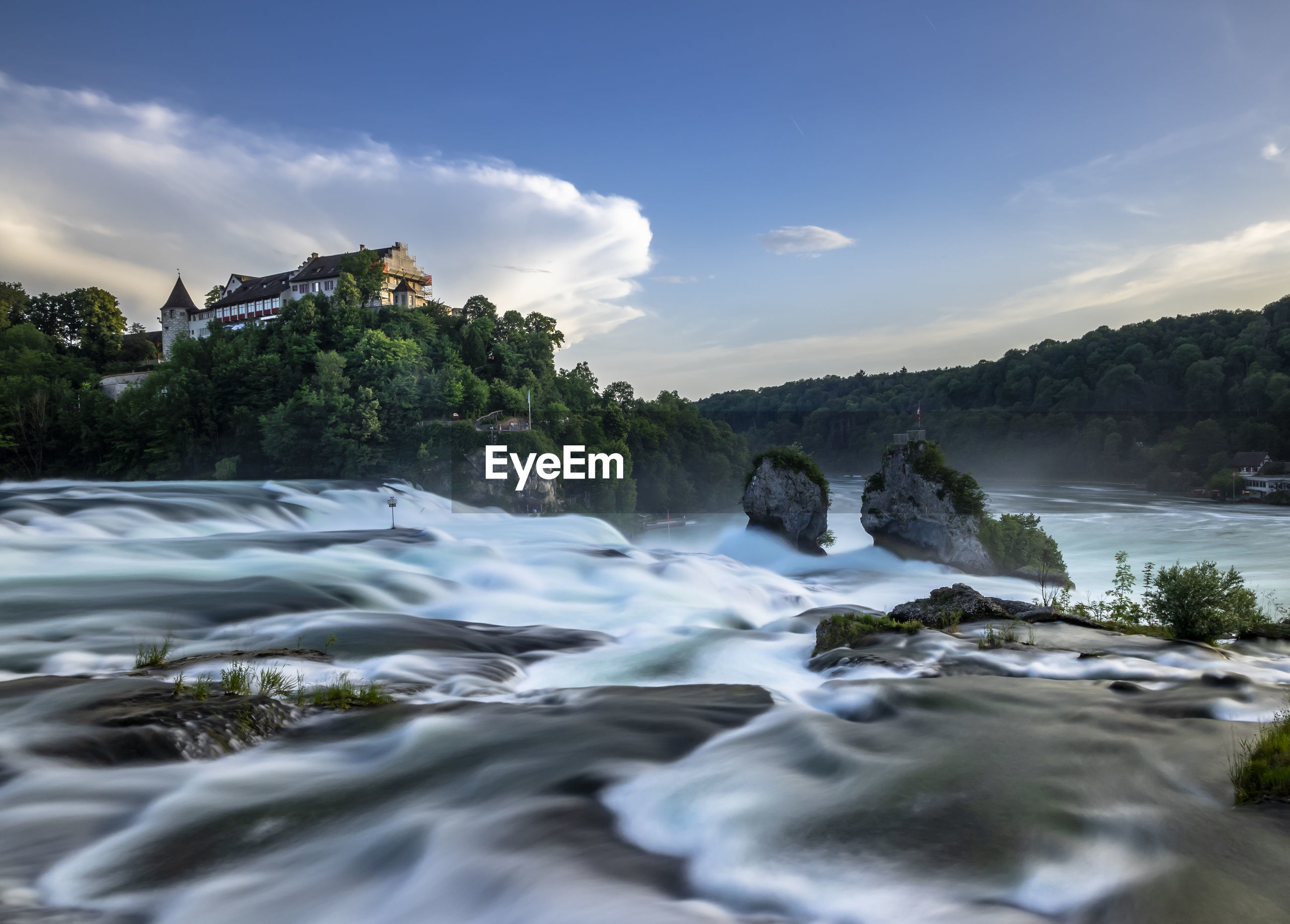 Scenic view of waterfall against clouds and sky