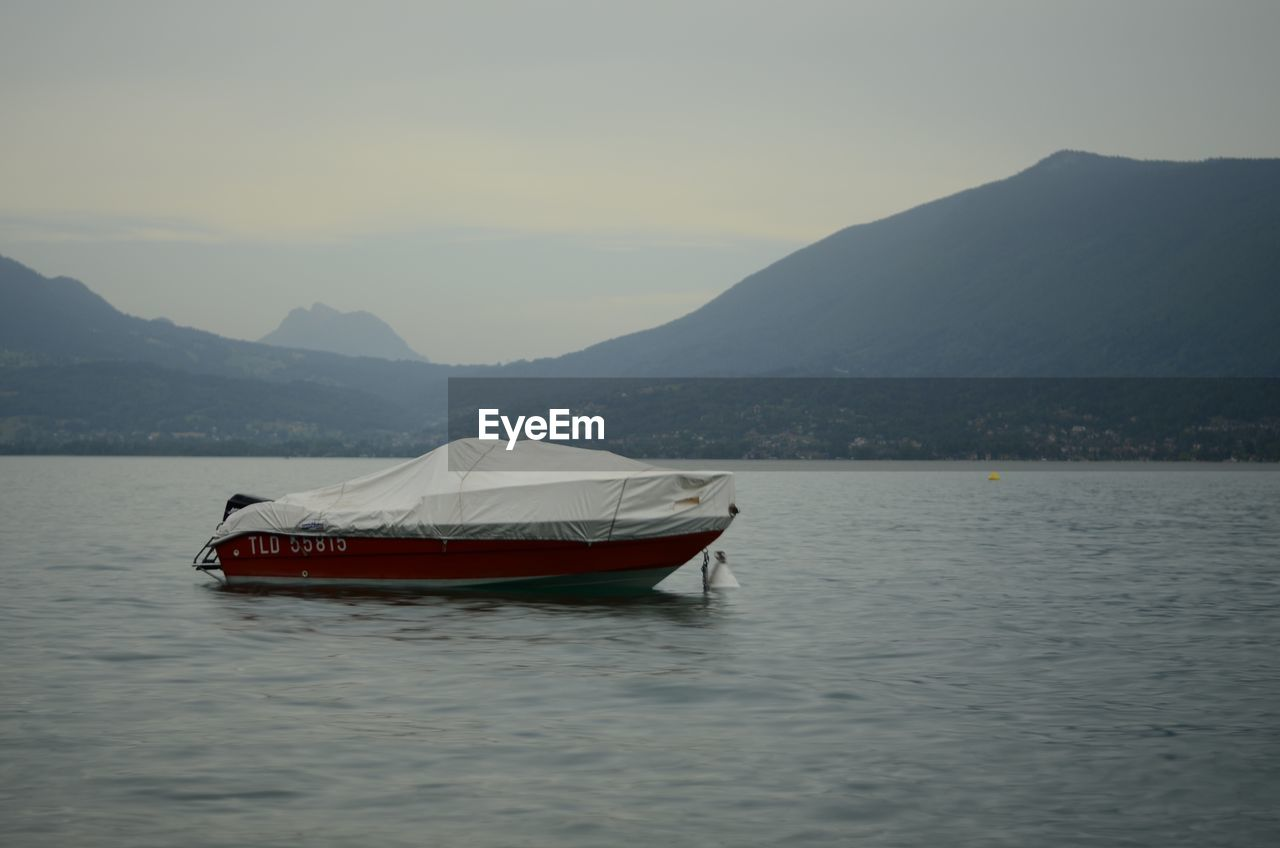 nautical vessel, mountain, transportation, mode of transportation, water, waterfront, sky, scenics - nature, beauty in nature, mountain range, tranquil scene, tranquility, nature, lake, non-urban scene, no people, travel, outdoors, rowboat