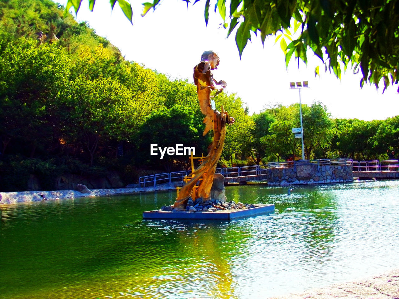 water, sculpture, statue, plant, tree, representation, art and craft, nature, human representation, day, lake, architecture, no people, fountain, creativity, sky, park, outdoors, park - man made space