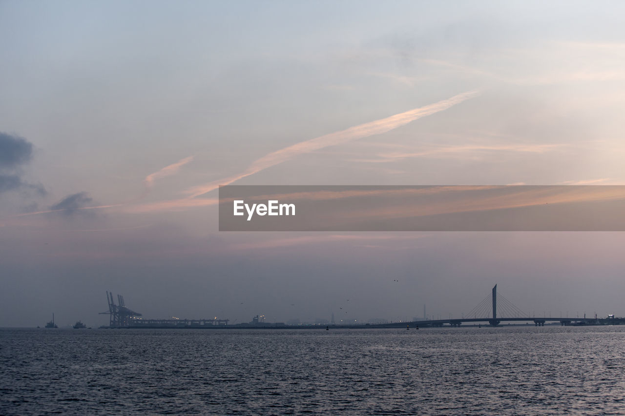Distant View Of Silhouette Bridge Over Sea Against Sky During Sunset