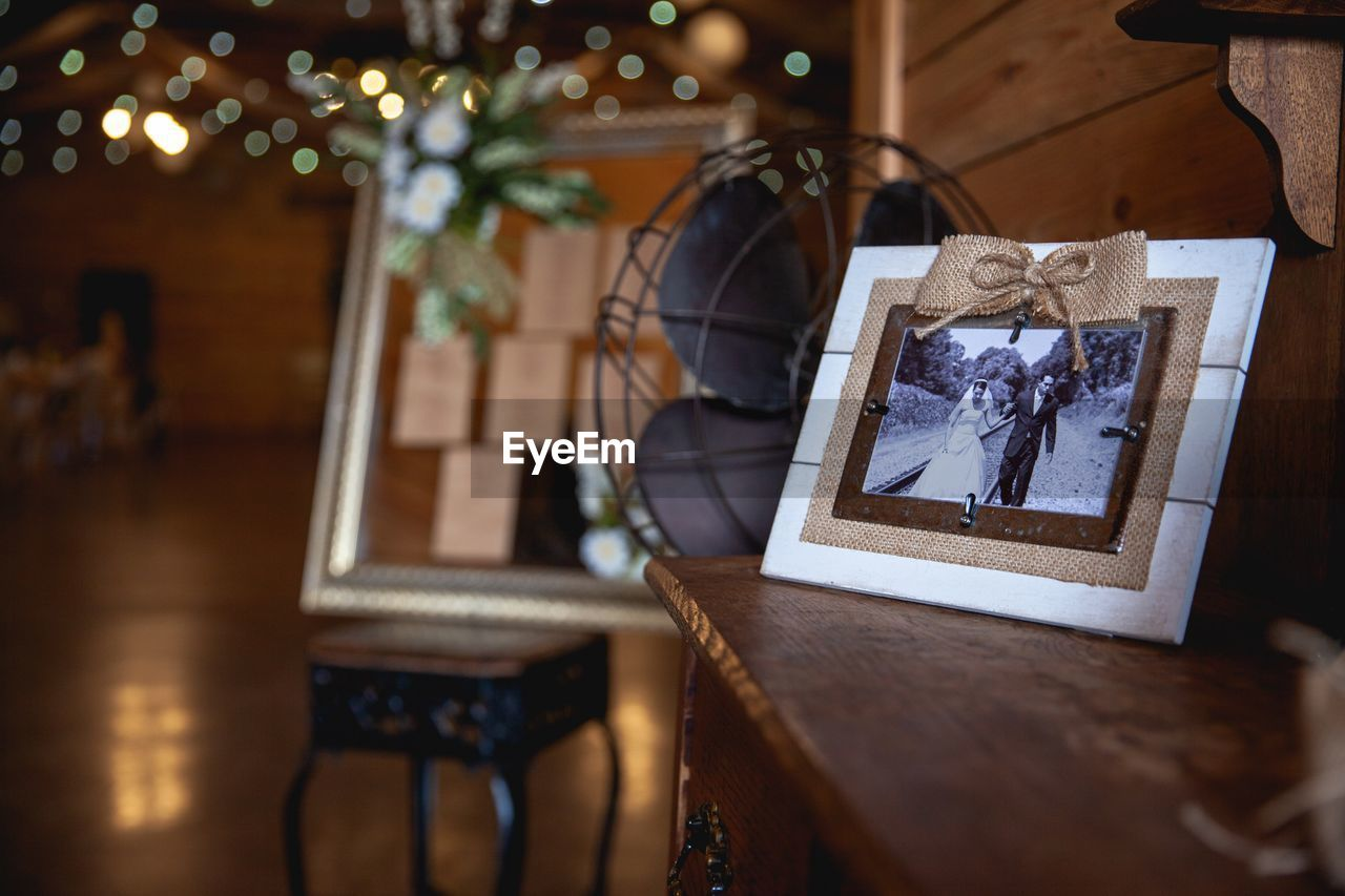 indoors, no people, wood - material, picture frame, frame, table, selective focus, home interior, seat, chair, decoration, architecture, focus on foreground, representation, photography themes, tree, human representation, lighting equipment, still life
