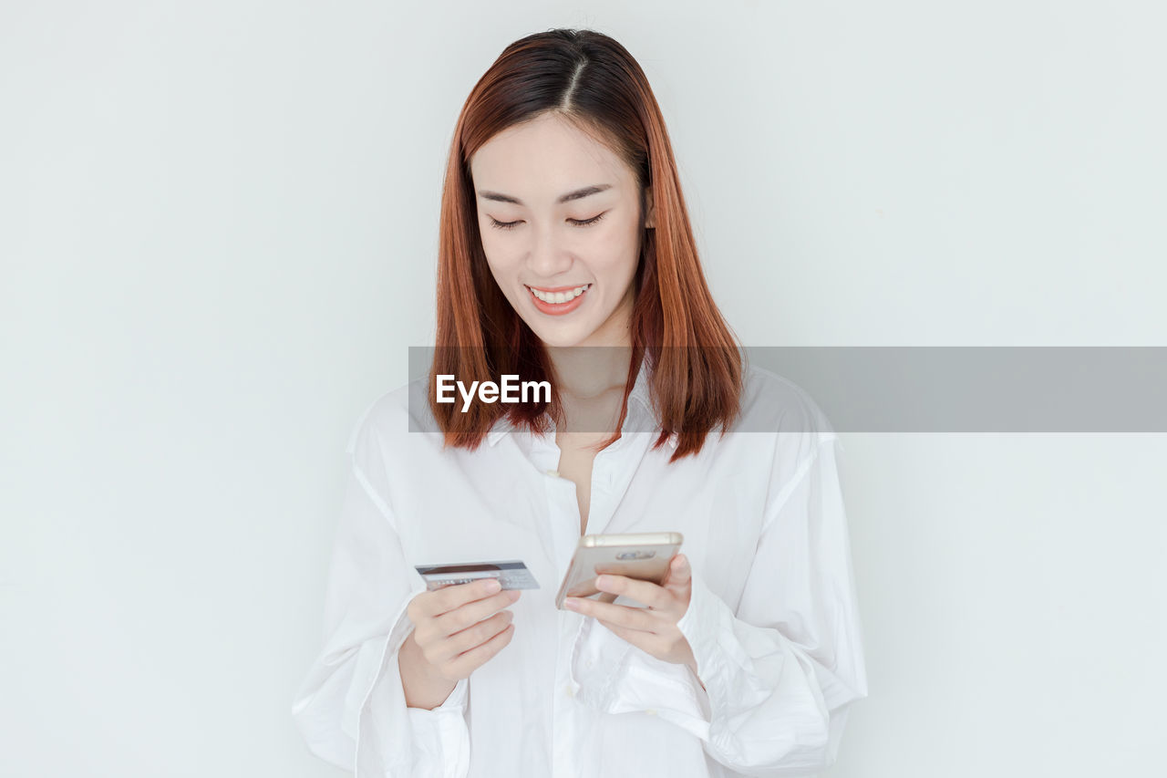 front view, one person, holding, indoors, young women, young adult, white background, technology, wireless technology, studio shot, waist up, communication, looking down, connection, standing, women, digital tablet, hairstyle, hair, beautiful woman