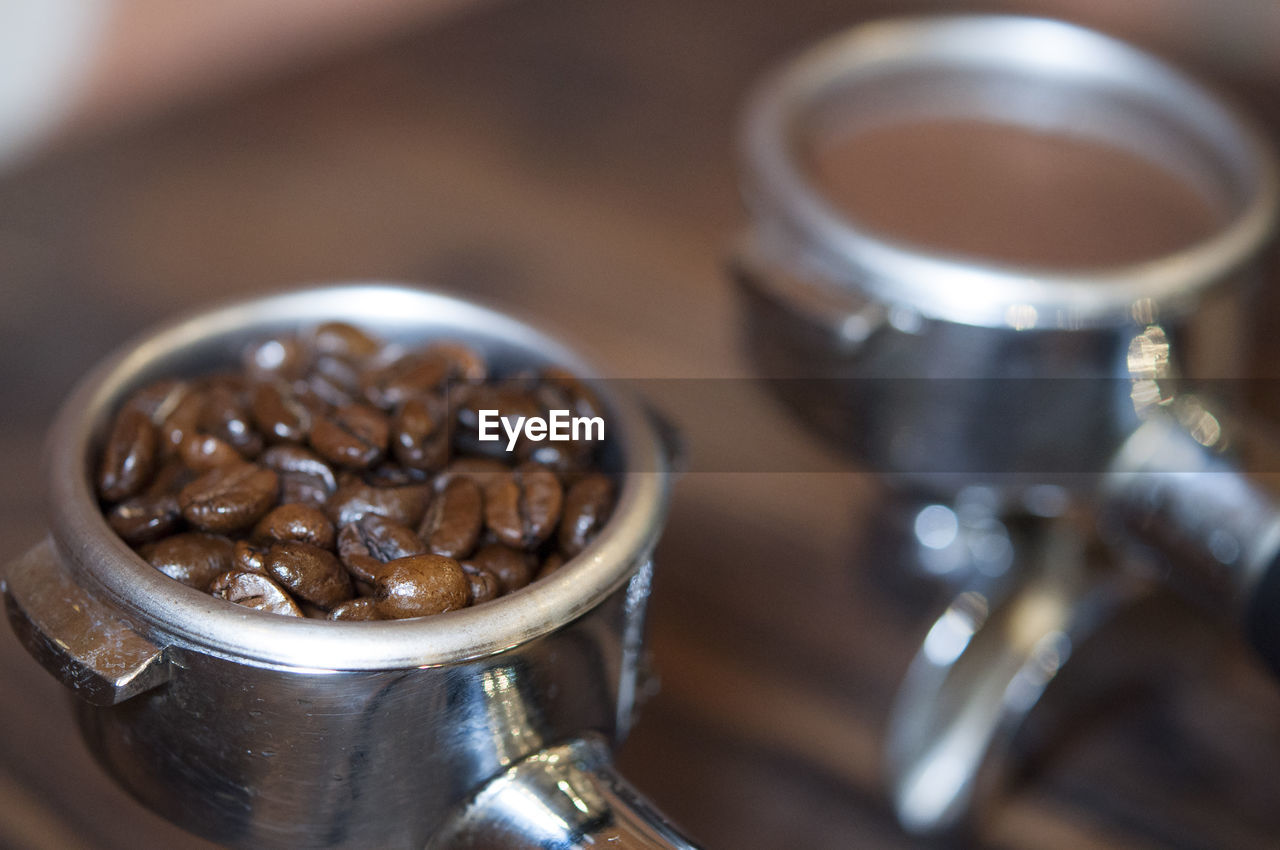 Close-Up Of Ground Coffee And Roasted Coffee Beans In Filters On Table