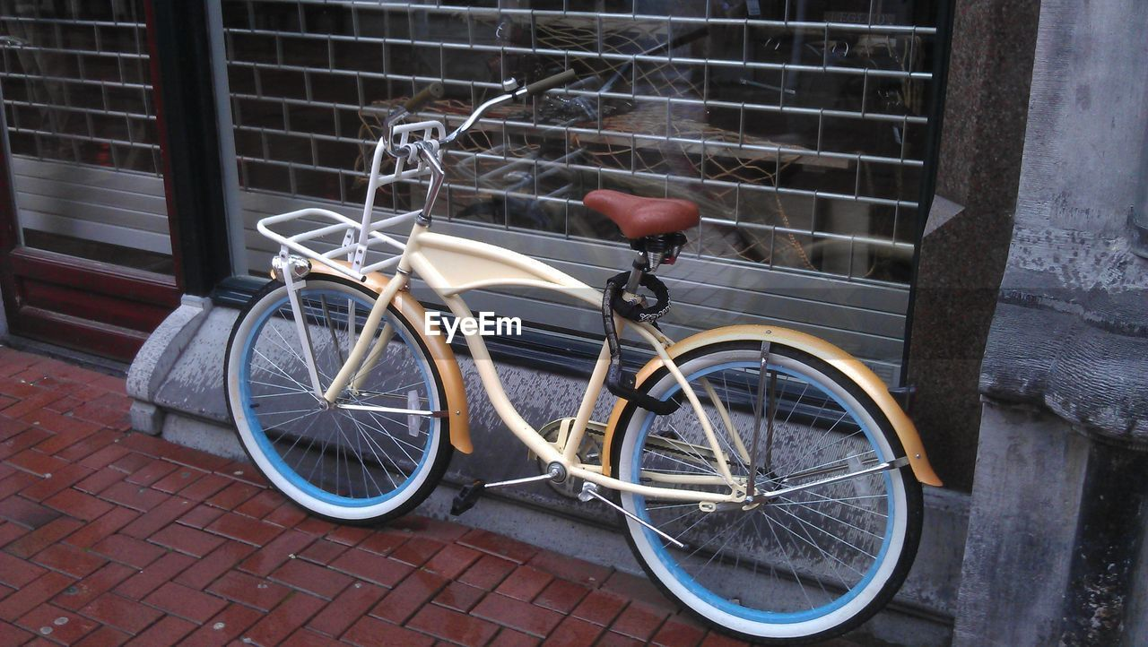 bicycle, transportation, land vehicle, mode of transportation, building exterior, stationary, architecture, built structure, city, street, day, no people, footpath, sidewalk, wall, brick, parking, outdoors, brick wall, metal, wheel, spoke