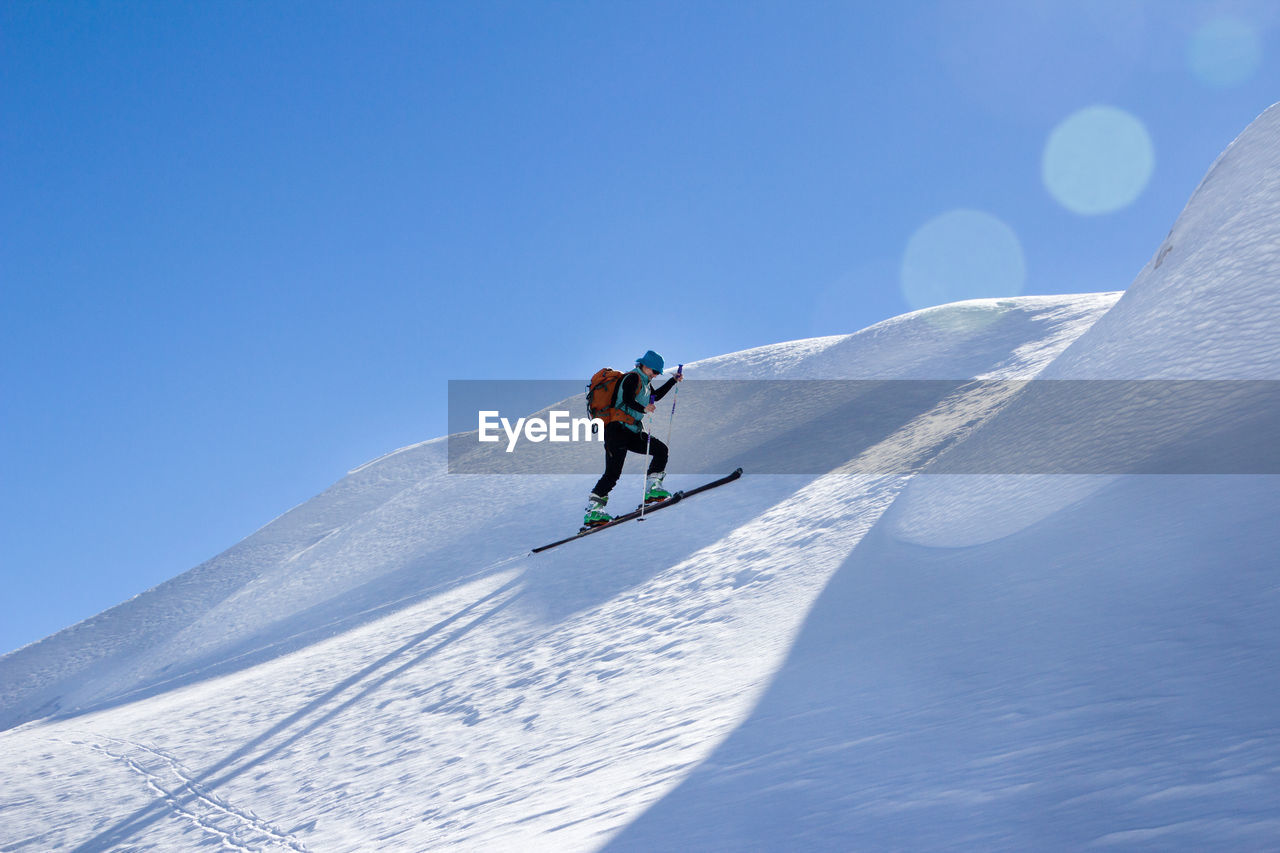 sport, snow, winter, cold temperature, leisure activity, winter sport, adventure, mountain, lifestyles, real people, sky, skiing, vacations, trip, day, one person, holiday, full length, snowcapped mountain, mountain range, outdoors, warm clothing