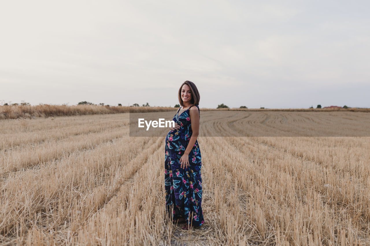 Portrait of smiling pregnant woman with hand on stomach standing on field