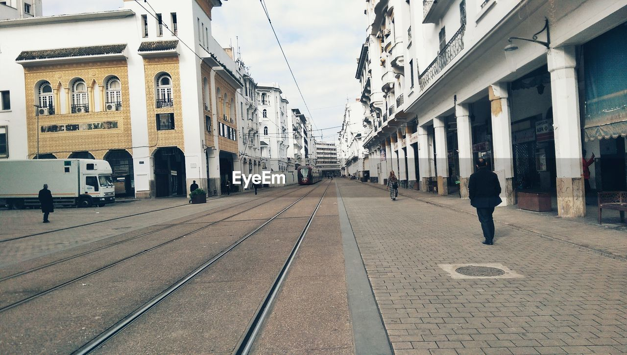 Rear View Of Man Walking On City Street