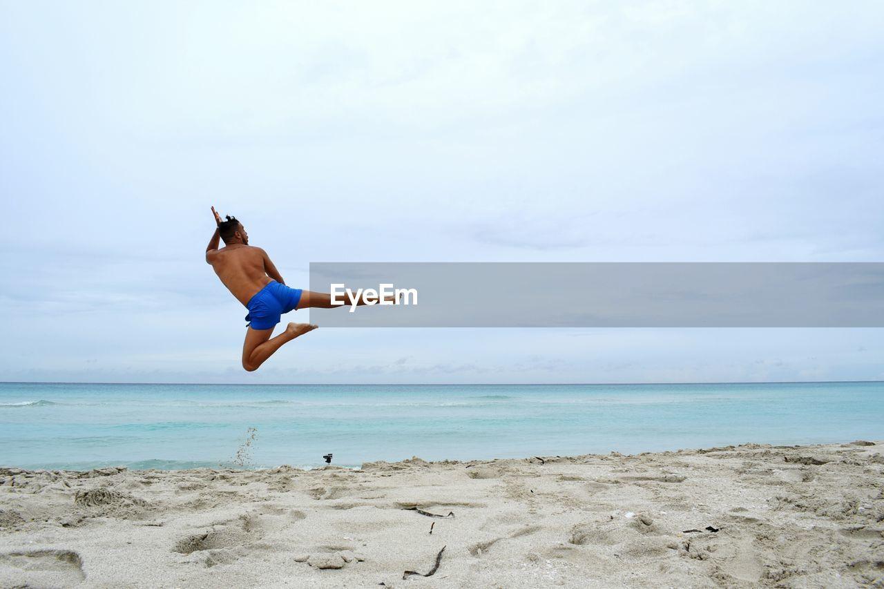 Shirtless Man Jumping On Beach Against Sky