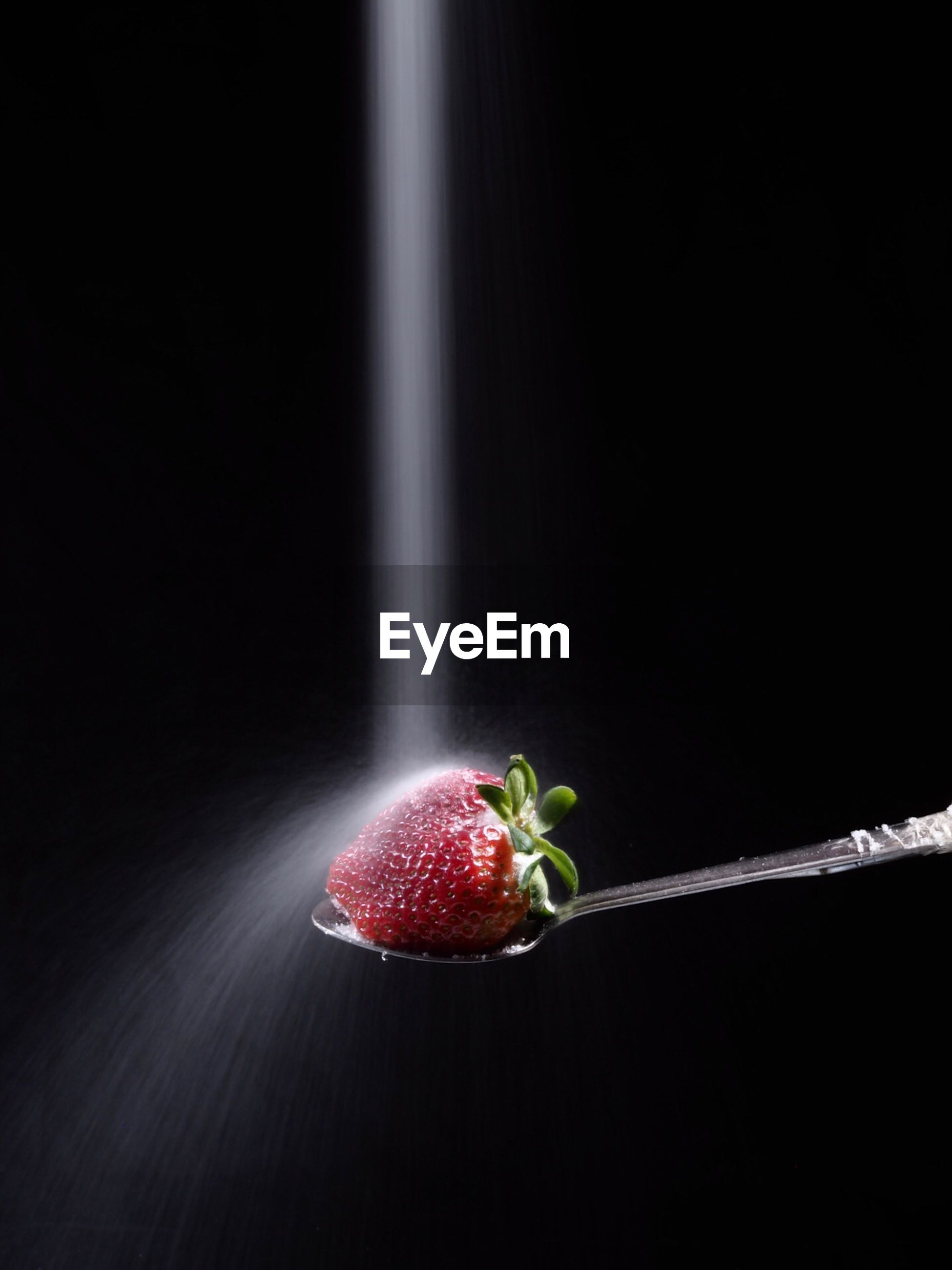 Close-up of water falling on strawberry in spoon against black background