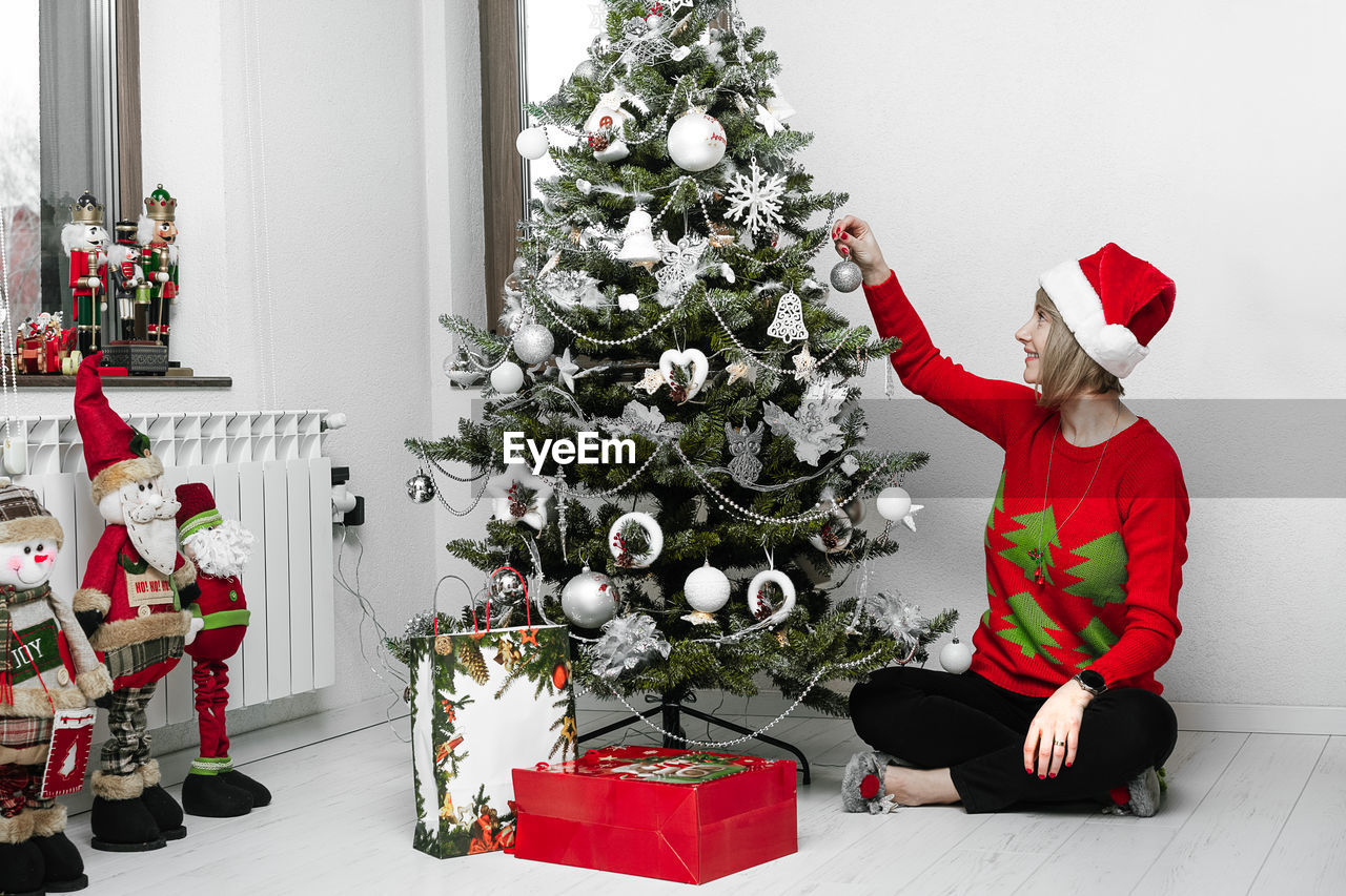 Woman Decorating Christmas Tree At Home