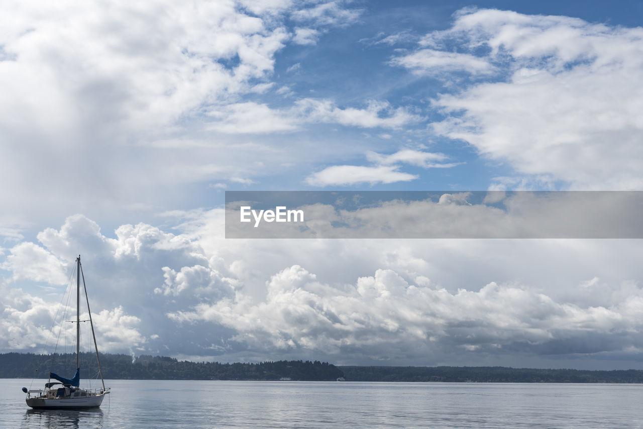 Sailboat moored at sea against sky