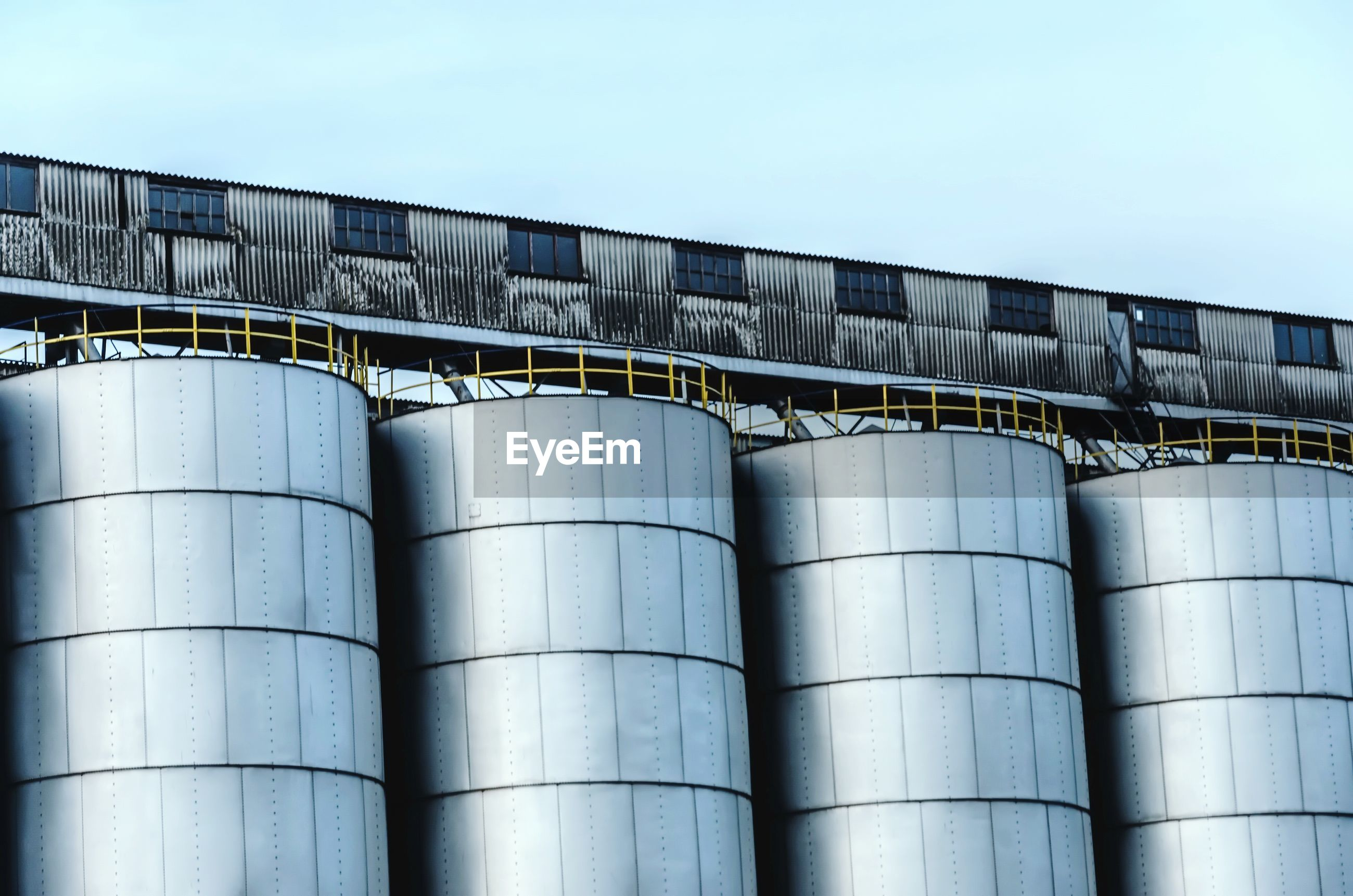 Low angle view of silos against sky