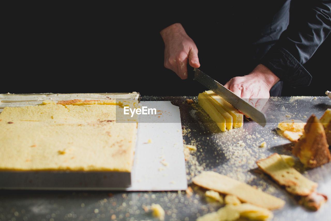 CLOSE-UP OF CHEF CUTTING SPONGE CAKE