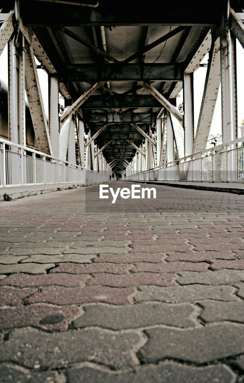architecture, bridge, built structure, connection, the way forward, diminishing perspective, transportation, bridge - man made structure, direction, no people, vanishing point, day, outdoors, surface level, metal, underneath, nature, in a row, architectural column, below, alloy, long, ceiling