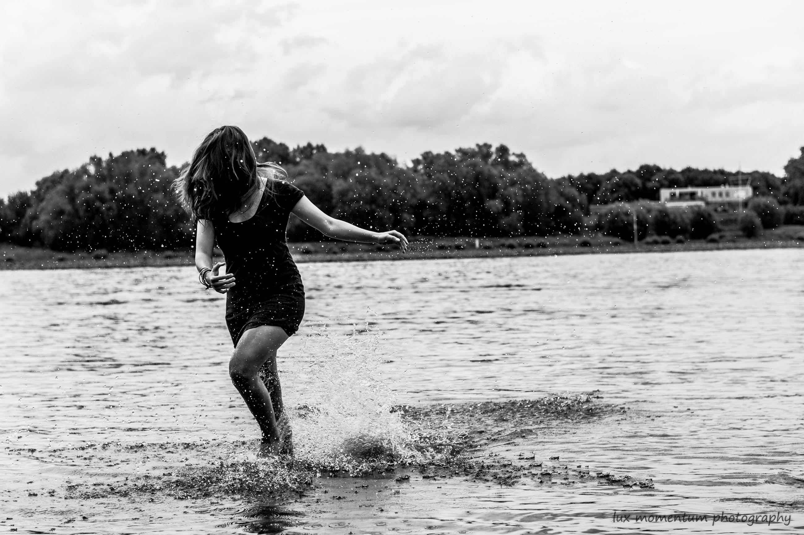 Woman wearing dress running at riverbank against sky