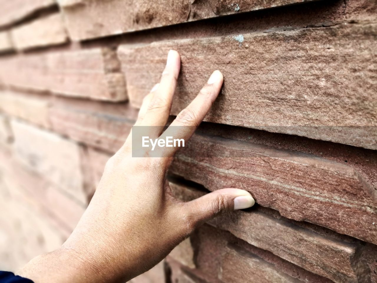 human hand, hand, human body part, wood - material, wall - building feature, real people, one person, finger, human finger, body part, day, close-up, wall, personal perspective, lifestyles, architecture, brick, outdoors, high angle view, human limb