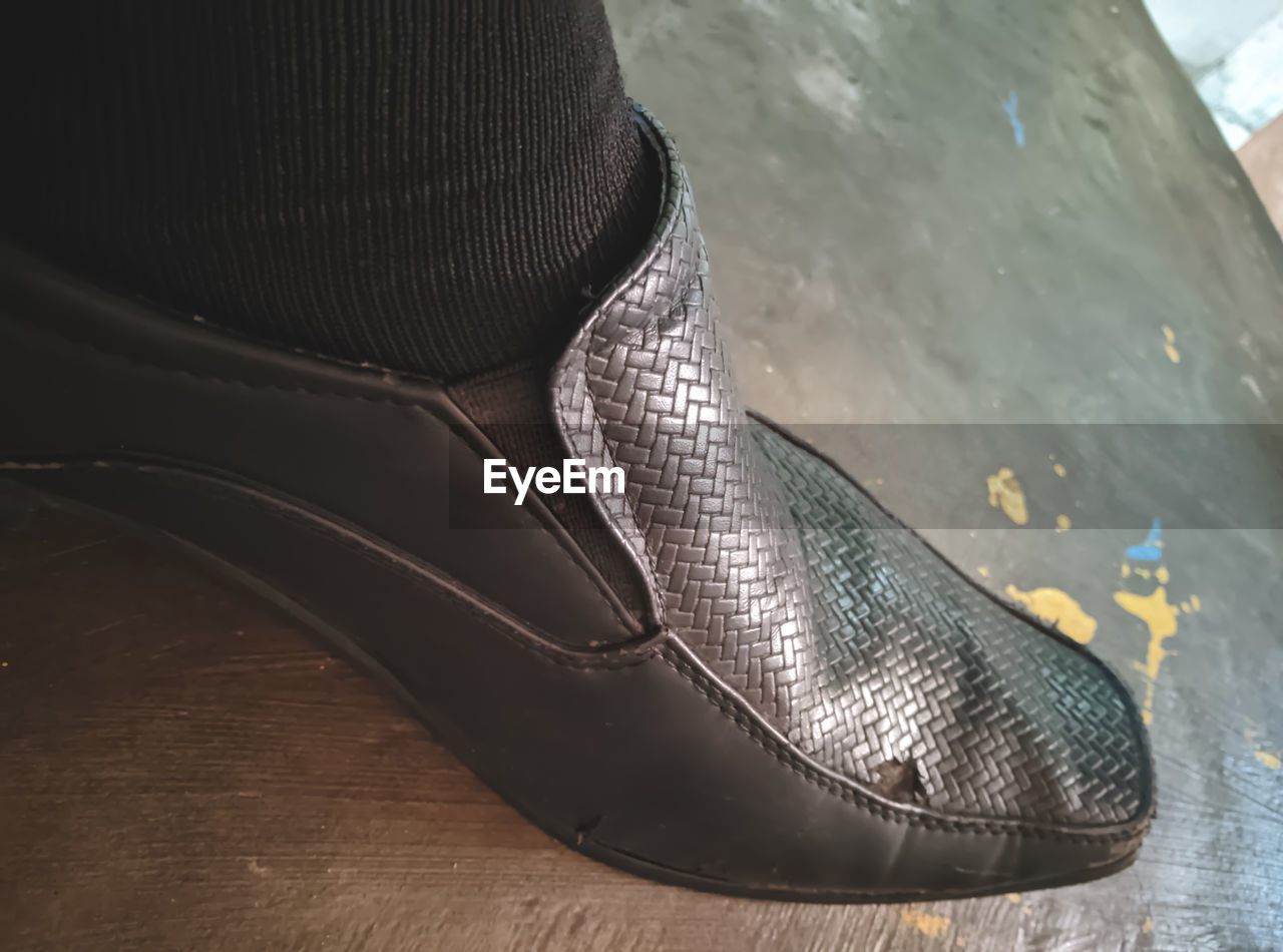 LOW SECTION OF PERSON WEARING SHOES IN HIGH HEELS